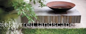 wooden seating and simple water feature complete this garden design